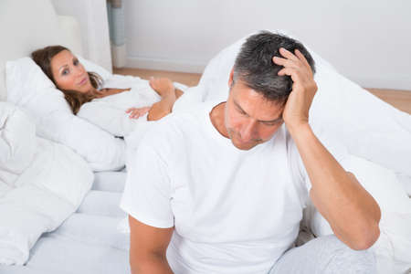 Woman Looking At Upset Man In Bedroom