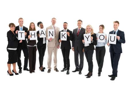 Foto für Full length portrait of smiling business team holding Thank You sign against white background - Lizenzfreies Bild