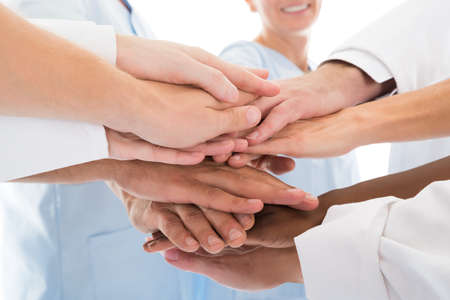 Photo pour Cropped image of medical team stacking hands against white background - image libre de droit