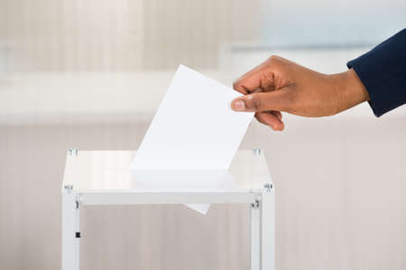 Close-up Of A Person's Hand Putting Ballot In Box
