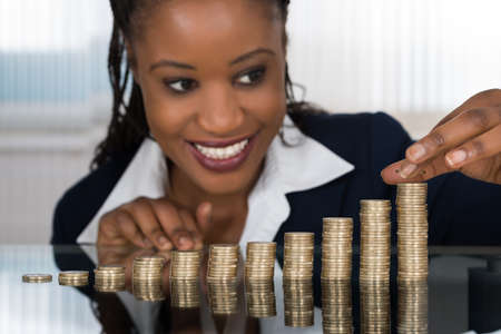 Close-up Of A Smiling African Businesswoman Making Stack Of Coins