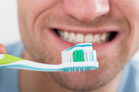 Photo pour Closeup of mid adult man brushing teeth - image libre de droit