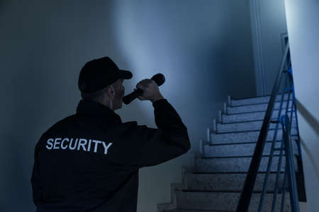 Rear view of security guard searching on stairway with flashlight in office building