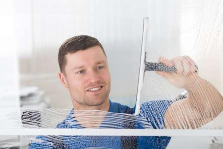 Photo pour Smiling mid adult worker cleaning soap sud on glass window with squeegee - image libre de droit
