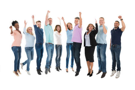 Photo for Full length portrait of creative business team celebrating success against white background - Royalty Free Image