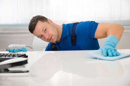 Photo pour Mid adult male janitor cleaning desk with sponge at office - image libre de droit