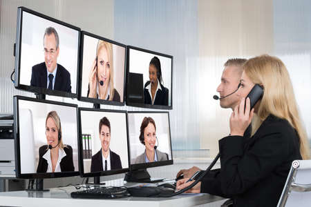 Photo pour Business people having conference call with multiple computer screens at table in office - image libre de droit