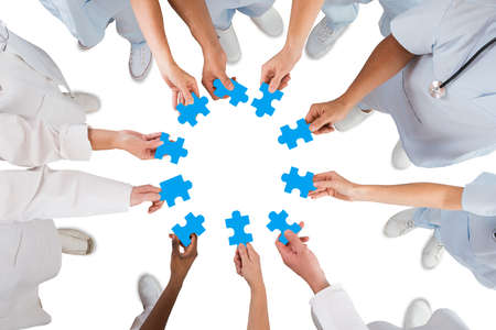Directly above shot of medical team holding blue jigsaw pieces in huddle against white background