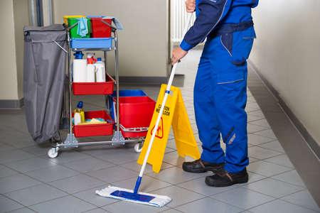 Foto de Low section of male janitor with broom cleaning office corridor - Imagen libre de derechos