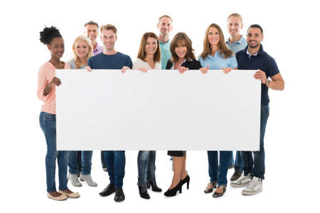 Foto de Full length portrait of confident creative business team holding blank billboard against white background - Imagen libre de derechos