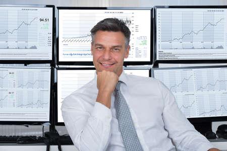 Photo pour Portrait of confident stock market broker leaning on desk at office - image libre de droit
