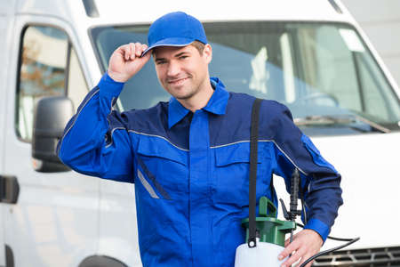 Photo for Portrait of confident pest control worker wearing cap against truck - Royalty Free Image