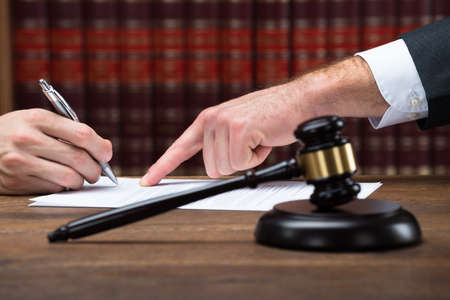 Photo pour Cropped hand of judge assisting client to sign legal document at table in courtroom - image libre de droit