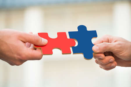 Photo for Cropped hands of businessmen joining jigsaw pieces outdoors - Royalty Free Image