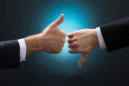 Photo pour Cropped hands of businessmen showing like and dislike signs against blue background - image libre de droit