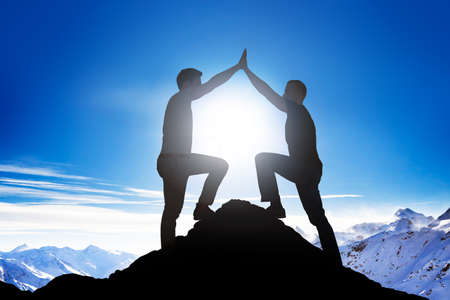 Photo for Side view of silhouette male friends giving high five on mountain peak - Royalty Free Image