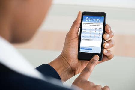 Photo pour Close-up Of A Businesswoman Filling Online Survey Form On Mobile Phone - image libre de droit