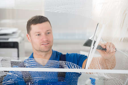 Foto de Smiling mid adult worker cleaning soap sud on glass window with squeegee - Imagen libre de derechos