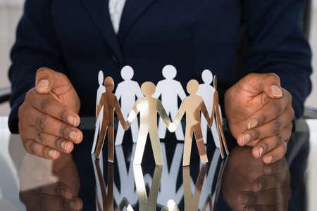 Photo pour Close-up Of Human Hand Protecting Cut-out Figures - image libre de droit