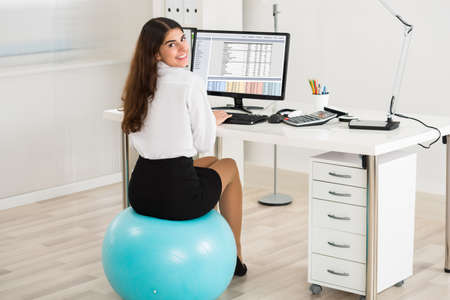 Portrait of happy young businesswoman using computer while sitting on exercise ball in office