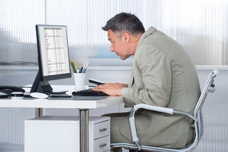 Photo pour Side view of concentrated businessman using computer at desk in office - image libre de droit