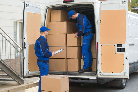 Photo pour Delivery man unloading cardboard boxes from truck while colleague writing on clipboard - image libre de droit
