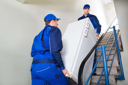 Photo pour Side view of movers carrying refrigerator while climbing steps at home - image libre de droit