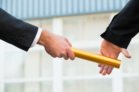 Cropped hand of businessman passing golden relay baton to colleague outdoors