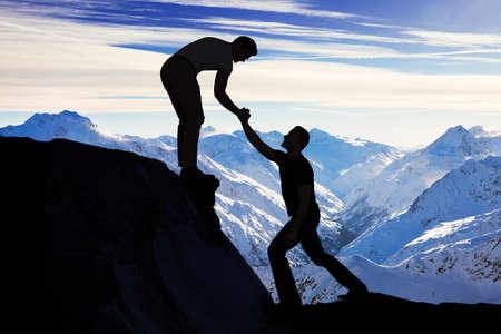 Photo pour Silhouette young man assisting male friend in climbing rock - image libre de droit