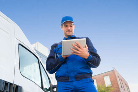 Photo pour Low angle view of delivery man using digital tablet by truck against sky - image libre de droit
