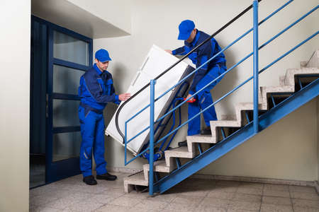 Photo pour Full length of male movers carrying refrigerator while climbing steps at home - image libre de droit