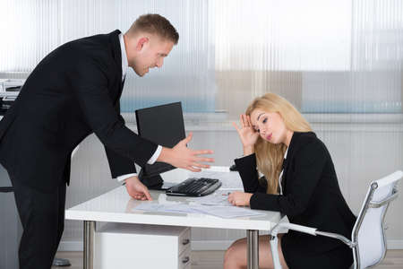 Foto de Boss shouting at female employee sitting at desk in office - Imagen libre de derechos