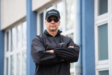 Photo for Portrait of confident mature security guard standing arms crossed outside building - Royalty Free Image