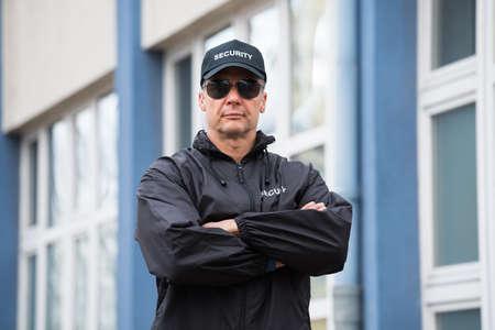 Photo pour Portrait of confident mature security guard standing arms crossed outside building - image libre de droit