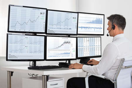 Photo pour Side view of stock market broker looking at graphs on multiple screens in office - image libre de droit