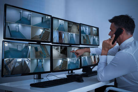Photo pour Side view of security system operator using walkie-talkie while looking at CCTV footage - image libre de droit