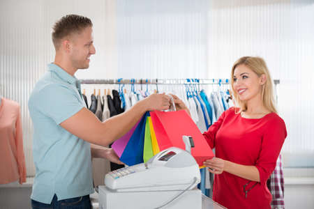 Photo pour Happy female customer taking shopping bags from salesman at counter in clothing store - image libre de droit