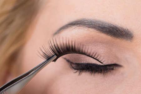 Foto de Close-up of false eyelashes being put on woman's eye - Imagen libre de derechos