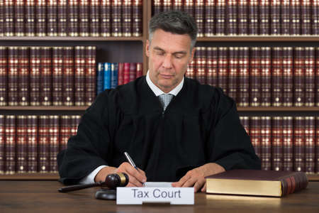 Tax court nameplate on table with judge writing on paper against bookshelf in courtroom