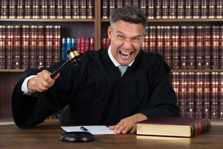 Photo pour Portrait of angry mature judge striking his gavel at table in courtroom - image libre de droit