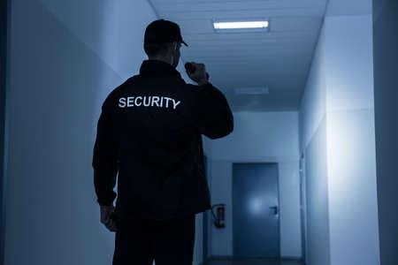 Photo pour Rear view of security guard with flashlight in building corridor - image libre de droit