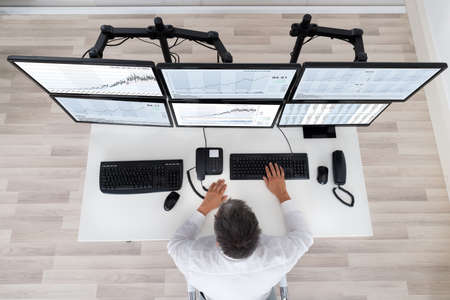 Photo pour Rear view of stock market broker looking at graphs at desk in office - image libre de droit