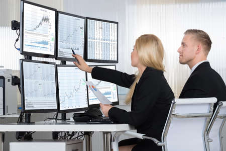 Photo for Financial workers analyzing data displayed on computer screens at desk in office - Royalty Free Image