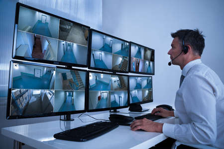 Photo pour Rear view of security system operator looking at CCTV footage at desk in office - image libre de droit