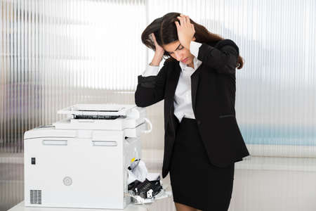 Photo pour Irritated young businesswoman looking at paper stuck in printer at office - image libre de droit