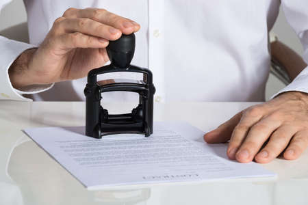 Midsection of businessman stamping contract document at office desk