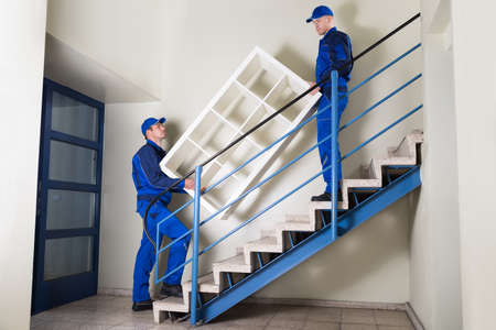 Photo pour Full length of young movers carrying shelf while climbing steps at home - image libre de droit