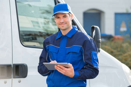 Photo pour Portrait of delivery man smiling using digital tablet by truck - image libre de droit