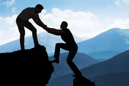 Foto de Silhouette young man assisting male friend in climbing rock - Imagen libre de derechos