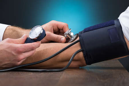 Photo for Cropped image of male doctor checking blood pressure of patient at table - Royalty Free Image